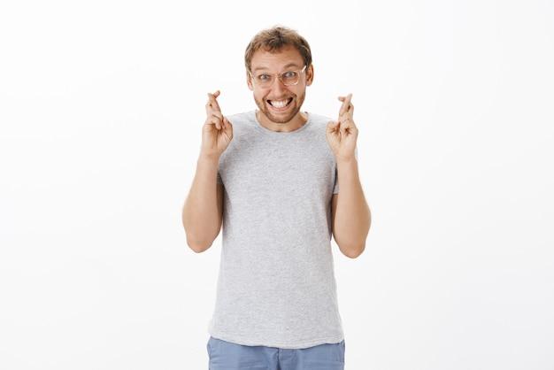 眼鏡をかけた剛毛のせっかちなハッピーでスリルのある楽観的な男性は、幸運と良い結果を待っている間ニヤリと笑うために驚いて陽気な交差指を見つめています