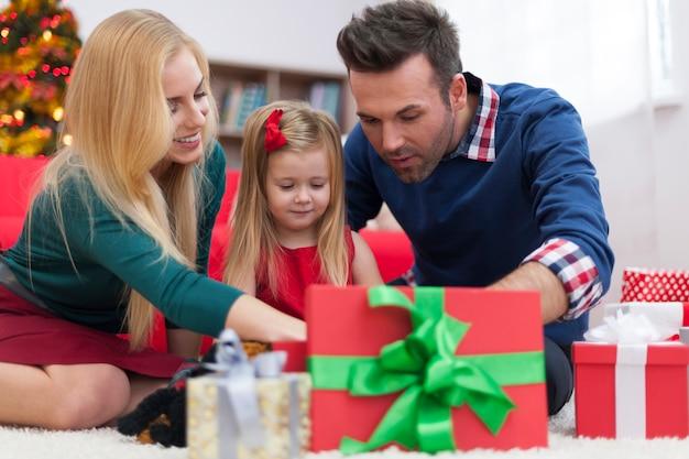 Нетерпеливая маленькая девочка открывает рождественские подарки с родителями