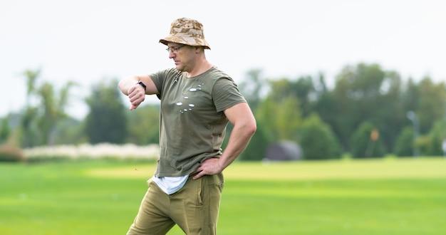 Нетерпеливый мужчина средних лет в тканевой шляпе и очках стоит на открытом воздухе в парке и смотрит на свои наручные часы в профиль крупным планом