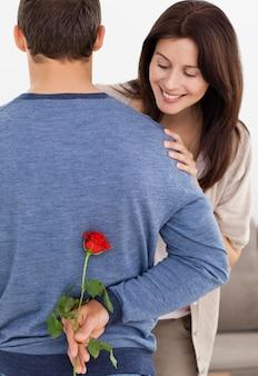 Impatiente woman looking at a flower hidden by her boyfriend
