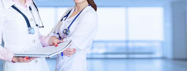 Impersonal portrait of a female doctor in front of a bright background
