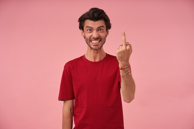 Impolite irritated young man with stubble in red tshirt shows rude fuck gesture using middle finger