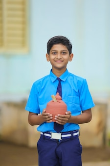 Importance of saving concept : smart indian little boy standing and holding piggy bank in hand at home.