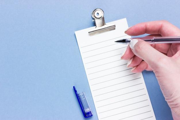 コピースペースと青色の背景に重要なビジネスチェックリスト、ショッピングリマインダーまたはプロジェクトの優先タスクリストの計画。女性の手でペン