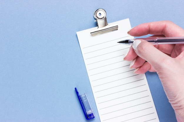 Important business checklist, planning for shopping reminder or project priority task list on blue background with copy space. pen in female hands