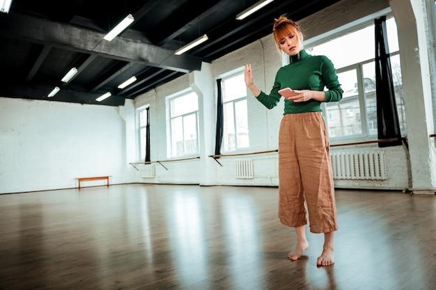 Важный звонок. рыжий профессиональный инструктор по йоге с серьезным видом говорит по телефону