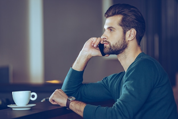 Important call. side view of handsome young man talking on mobile phone while sitting at bar counter