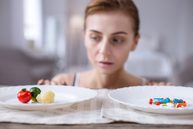 重要な選択。彼女の選択をしながら野菜とプレートを見て悲しい若い女性