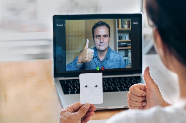 自家製のイヤリングを見せている認識されていない職人とビデオ通話をしている重要なクライアント。