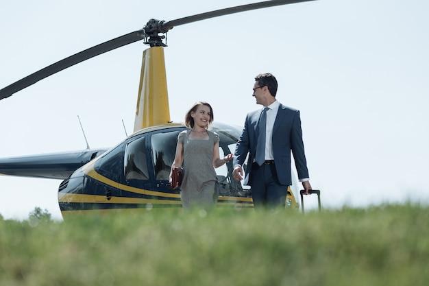 重要な会話。彼のヘリコプターの飛行の後に彼に会った彼女のビジネスパートナーと話している明るい若い女性