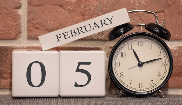 Important date, february 5, winter season. calendar made of wood on a background of a brick wall. retro alarm clock as a time management concept.