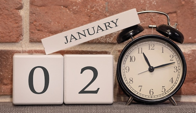 Important date, january 2, winter season. calendar made of wood on a background of a brick wall. retro alarm clock as a time management concept.