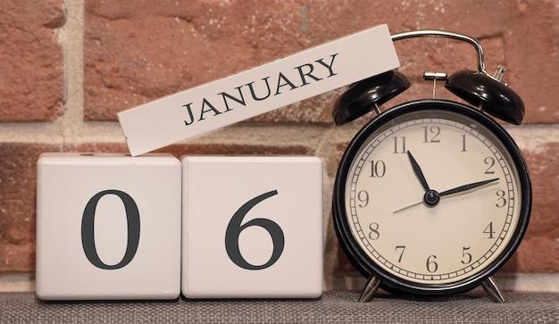 重要な日付、1月6日、冬のシーズン。レンガの壁の背景に木で作られたカレンダー。時間管理の概念としてのレトロな目覚まし時計。