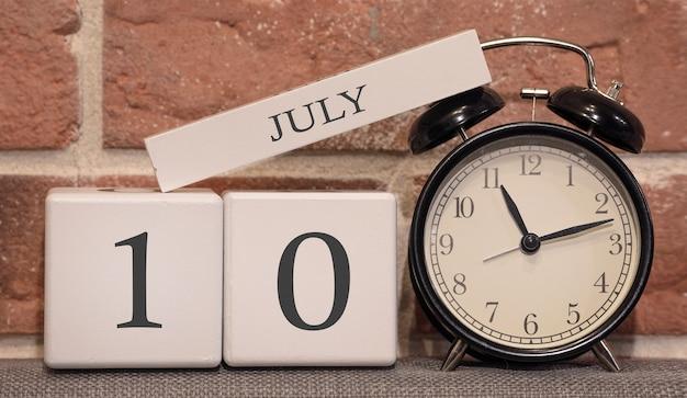 Важная дата, 10 июля, летний сезон. календарь из дерева на фоне кирпичной стены. ретро будильник как концепция управления временем.