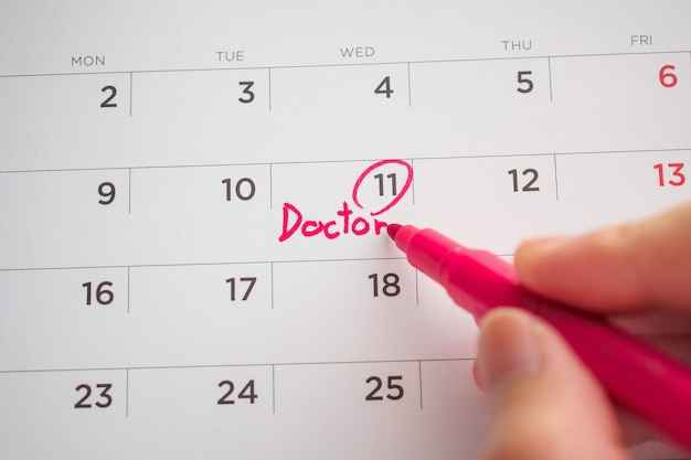 Important doctor appointment schedule write on white calendar page date close up