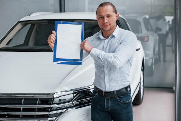 重要な文書。マネージャーは紙を手にして現代の白い車の前に立つ