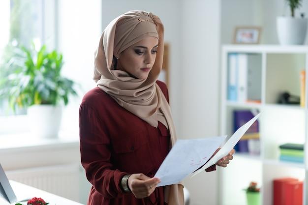 重要なドキュメント。仕事中に重要な文書を読んでヒジャーブを身に着けている魅力的な女性