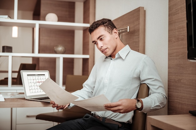Important documents. dark-haired smart prosperous man wearing striped shirt reading important documents
