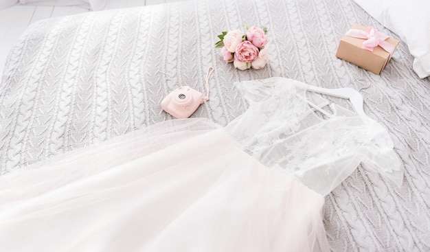Important elements of the wedding day. white amazing stunning wedding dress and shoes lying on the bed near the pink camera and bouquet in the bedroom