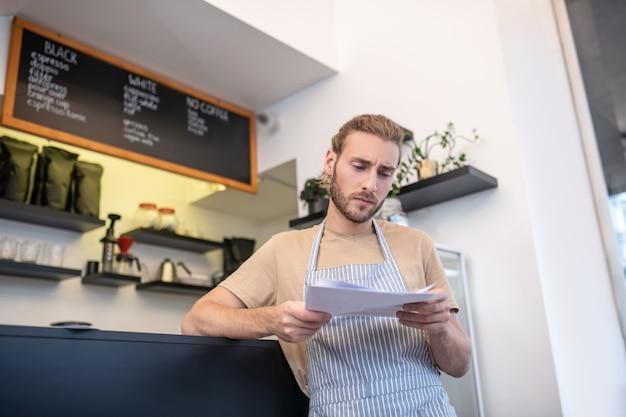중요한 정보. 그의 카페에 서있는 중요한 문서를 읽고 줄무늬 앞치마에 걱정 심각한 남자