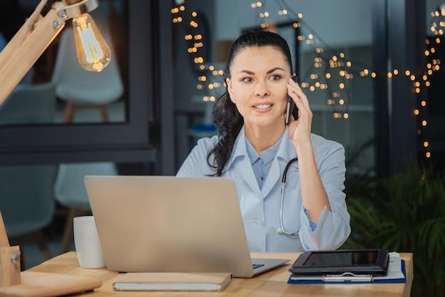 重要な問題。彼女のラップトップの前に座って、仕事について話している間電話で会話しているインテリジェントな素敵な女性医師