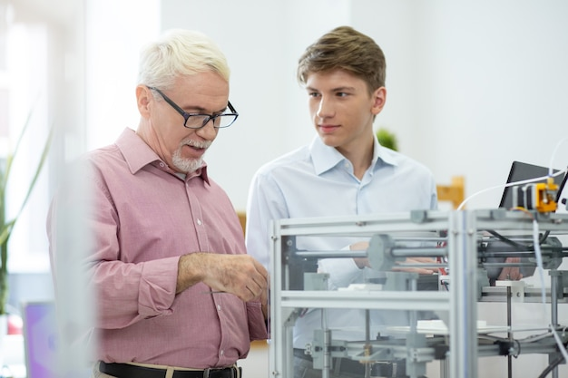 重要な教訓。男性が注意深く彼の話を聞いている間、彼のインターンに3dプリンターを調べる方法を示す陽気なシニアエンジニア