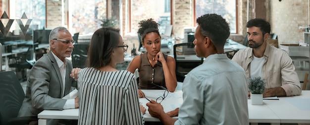 Важная встреча группы деловых людей, которые что-то обсуждают и работают вместе, сидя