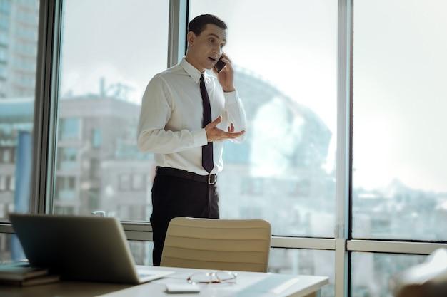 重要な交渉。彼のオフィスの窓の近くに立って、彼のパートナーと交渉して、感情的に電話で話している楽しいビジネスマン