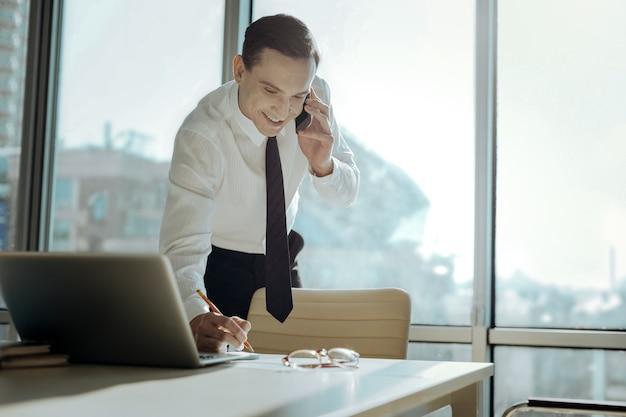 重要な注意事項。彼のオフィスのテーブルの近くに立って、電話で彼のパートナーと交渉しながらメモをとる魅力的な陽気な若い幹部
