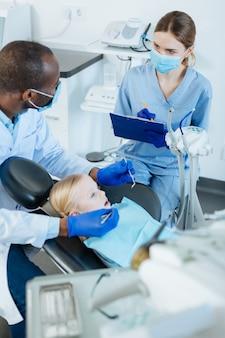 重要な注意事項。小さな患者の口腔を調べている間、歯科医の診断と推奨事項を書き留める楽しい若い女性看護師