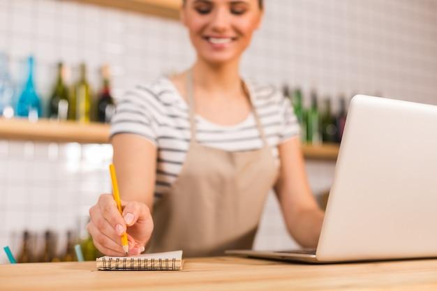 重要な注意事項。素敵な喜んでポジティブな女性によって使用されている間、テーブルの上に横たわっている小さなノートの選択的な焦点