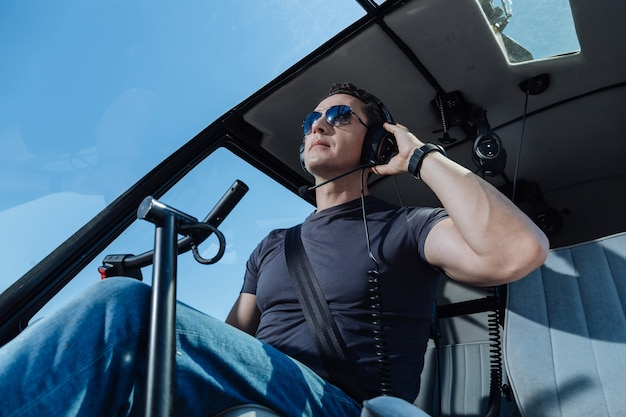 Important orders. serious young helicopter pilot using headphones and listening to the air traffic controller before starting the flight