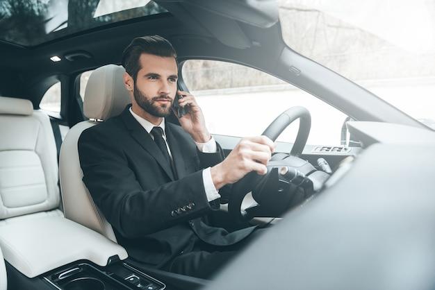 Важный телефонный разговор. красивый молодой бизнесмен разговаривает по своему смартфону с серьезным лицом во время вождения автомобиля