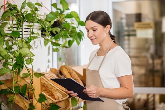 Важная точка. внимательная вовлеченная женщина в фартуке смотрит на папку с документами, стоящую возле прилавка в пекарне