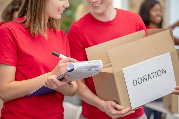 중요한 점. 기부 상자와 자선 센터에서 문서를 작성하는 근처에 서있는 소녀를 들고있는 남자