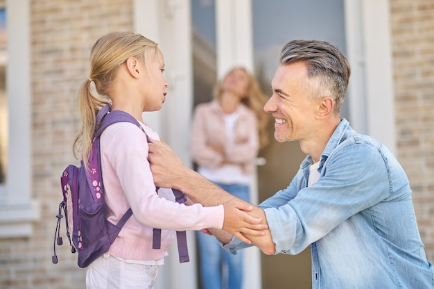 Important point. smiling caring middle-aged man crouching near his little daughter with backpack and wife in distance near house