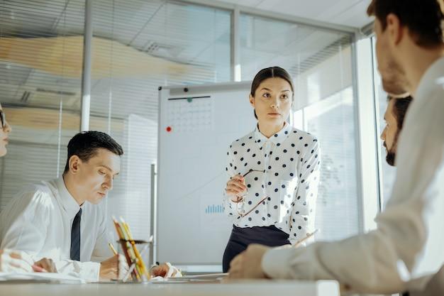 重要なスタッフ調査。同僚と毎日ミーティングを行い、契約の変更に関連する彼らのフィードバックに耳を傾ける楽しい女性の上司