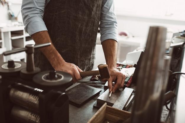 仕事の重要な段階。ハンマーを使って作業台で新製品を作るエプロンを身に着けている男性の金細工職人。ジュエリー作りのプロセス。仕事。ジュエリーワークショップ。
