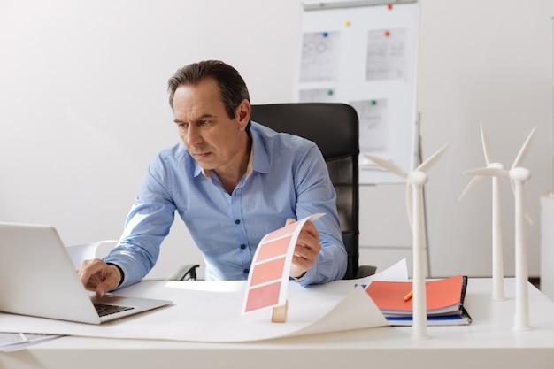 중요한 작업. 테이블에 앉아 노트북을 사용하는 동안 풍력 터빈 프로젝트를 진행하는 전문가 엔지니어