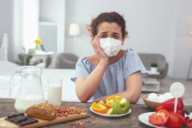 不可能な選択。複数の食物アレルギーに苦しんでいる間、彼女の不快感を引き起こし、彼女の食物選択を制限している間、若い動揺しているように見える女性は不幸を感じています