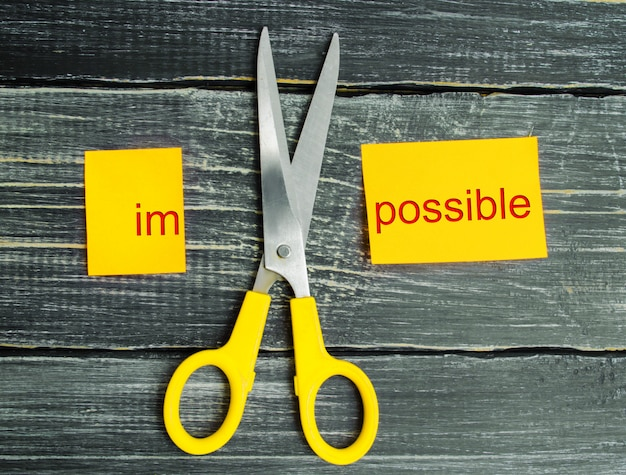 Impossible is possible concept. card with the text impossible, scissors cut a word to them.