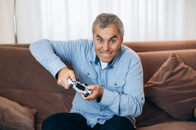倒せない成熟した男は彼の好きなゲームをプレイすることに完全に夢中になっています。彼はゲーム機のボタンを強く押します。背景のリビングルーム。楽しい時間を過ごしている男性ゲーマー。