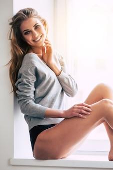 Невозможно устоять перед этой красотой. красивая молодая женщина, глядя в камеру с улыбкой, сидя на подоконнике дома