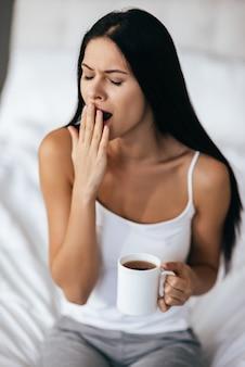 Проснуться невозможно! молодая красивая женщина с длинными темными волосами держит чашку и зевает