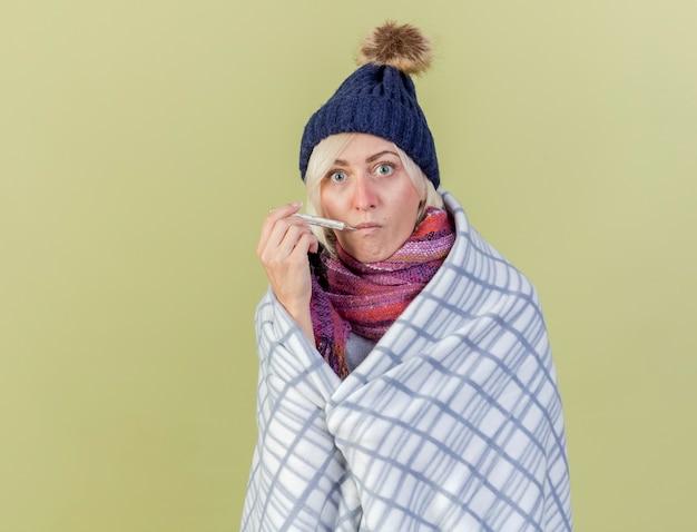 격자 무늬에 싸여 겨울 모자와 스카프를 착용하는 impresed 젊은 금발의 아픈 여자는 올리브 녹색 벽에 고립 된 입에 온도계를 넣습니다