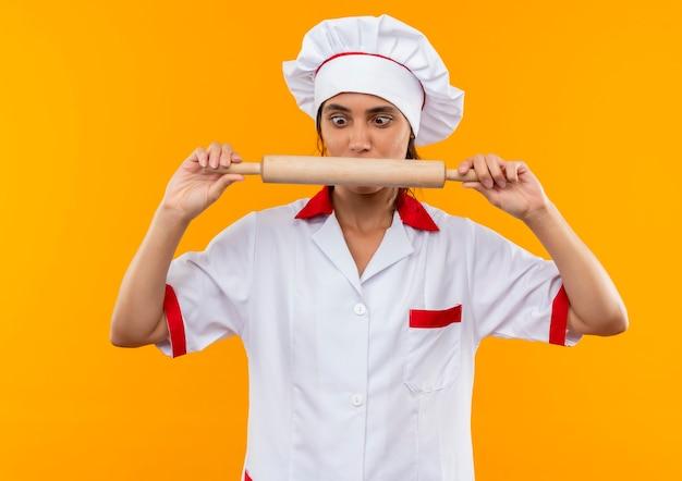 Представленная молодая женщина-повар в униформе шеф-повара держит и смотрит на скалку на изолированной желтой стене