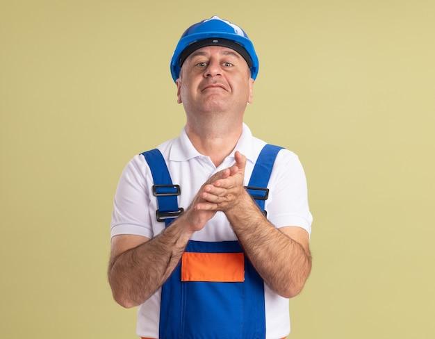 L'uomo adulto del costruttore impressionato in uniforme batte le mani isolate sulla parete verde oliva