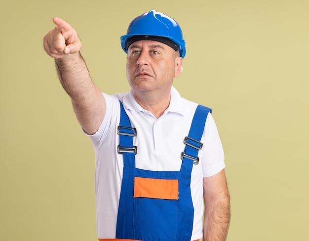 Uomo adulto impressionato del costruttore in sguardi uniformi e punti sul lato isolato sulla parete verde oliva
