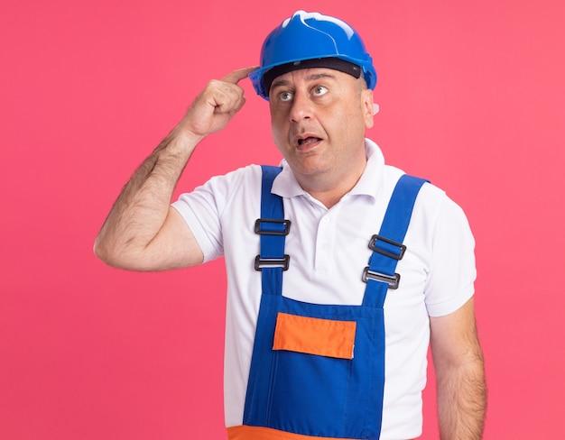 L'uomo caucasico adulto del costruttore impressionato in uniforme mette il dito sul casco di sicurezza sul colore rosa