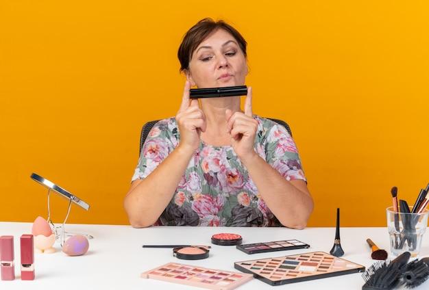 Donna caucasica adulta impressionata seduta al tavolo con strumenti per il trucco che tengono e guardano il mascara isolato sulla parete arancione con spazio di copia